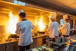 Restaurant kitchen releasing smoke and grease into the air systems