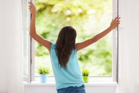 woman opening windows to improve indoor air quality